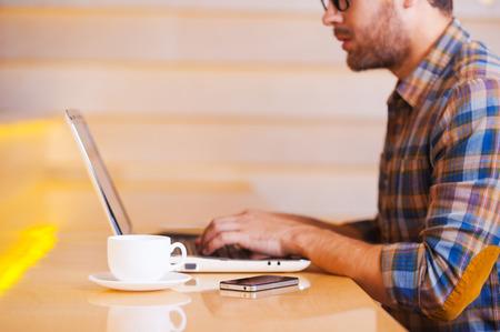 コーヒー店で働いてください。サイドビューは、喫茶店に坐っている間のラップトップに取り組んで思いやりのある若い男の画像をトリミング 写真素材