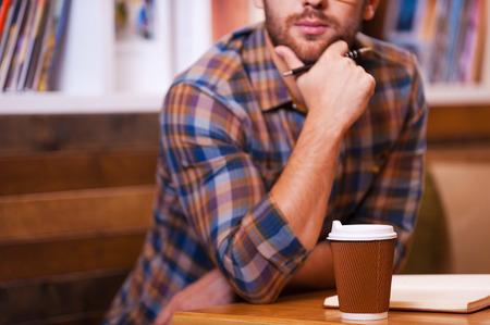 people thinking: Perdido en pensamientos. Primer plano de hombre de mano que sostiene joven pensativa en la barbilla mientras se est� sentado en el escritorio en la biblioteca Foto de archivo