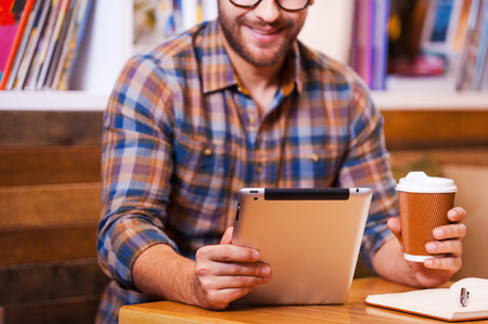 bookshelf digital: Digital age student. Close-up of cheerful young man holding coffee cup and looking at his digital tablet while sitting at the desk with bookshelf in the background