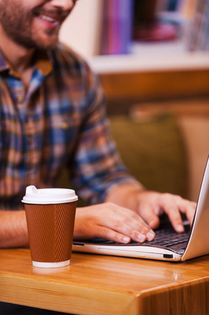 internet shop: Surfing the Net. Close-up of young man working on laptop and smiling while sitting at the desk with focus on coffee cup Stock Photo