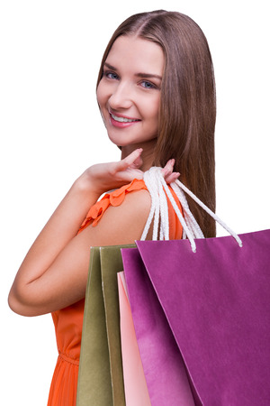 Beautiful shopaholic. Portrait of a beautiful young woman looking over shoulders and holding shopping bags while standing against white background photo