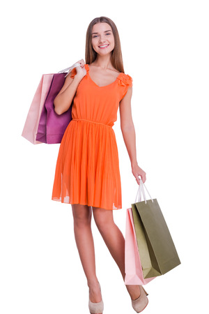 After a day shopping. Beautiful young woman holding shopping bags and smiling while standing against white background photo