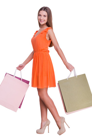 Excellent shopping. Full length of beautiful young woman carrying shopping bags and smiling while standing against white background photo