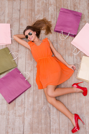 laying: Beautiful shopaholic. Top view of beautiful young woman in sunglasses holding hand in hair and smiling while lying on the floor among shopping bags