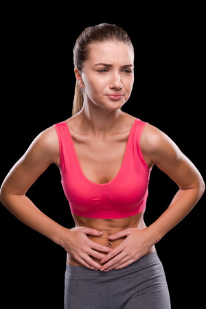 expressing negativity: Stomachache. Frustrated young woman touching her abdomen and expressing negativity while standing against black background Stock Photo