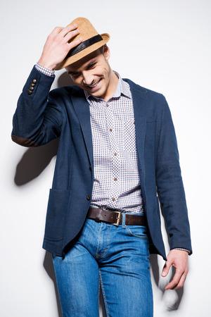 modelos hombres: En su propio estilo. Apuesto joven en ropa de sport elegante que ajusta su sombrero y sonriendo mientras est� de pie contra una pared