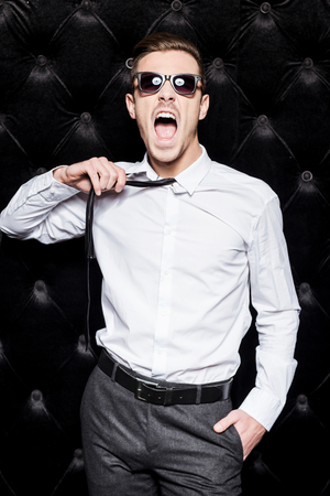 hard work: Work hard play hard! Handsome young man in sunglasses taking off his necktie and shouting while standing against black background Stock Photo