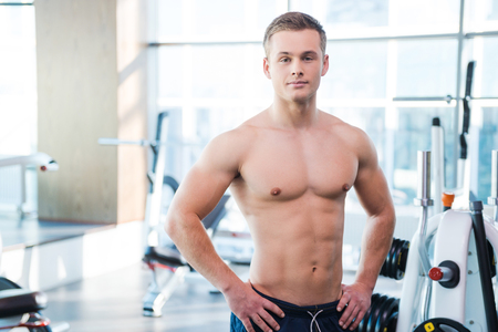 only the biceps: Strong and muscular. Confident young muscular man holding hands on hip and looking at camera while standing in gym