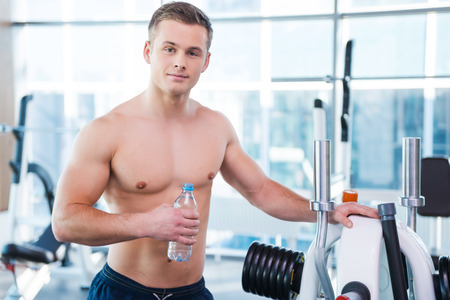 shirtless guy: Strong and muscular. Confident young muscular man holding bottle with water and looking at camera while standing in gym