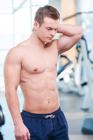 expressing negativity: Feeling pain after workout. Frustrated young muscular man touching his neck and expressing negativity while standing in gym