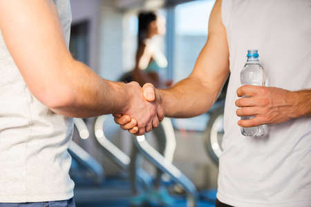 sports coach: Meeting friend in gym. Two men shaking hands while standing in gym