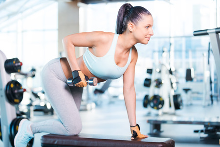 weightlifting equipment: Weight training. Side view of confident young woman exercising with dumbbells in gym Stock Photo