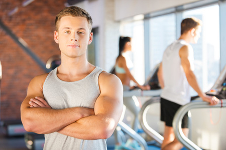 machine man: Strong and confident. Handsome young man keeping arms crossed and looking at camera while people walking by treadmill in the background