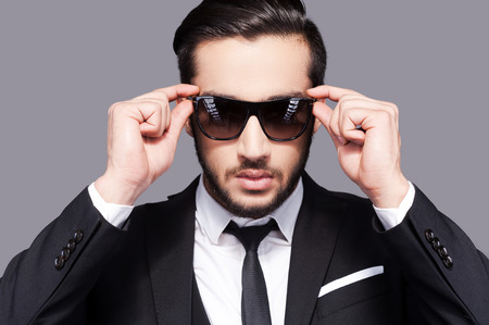 adjusting: I put the man in manly. Portrait of handsome young man in formal wear adjusting his sunglasses while standing against grey