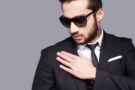 modelos hombres: Se utiliza para lucir perfecta. Apuesto joven en gafas de sol y ropa formal que tocan el hombro con la mano mientras est� de pie contra el fondo gris Foto de archivo