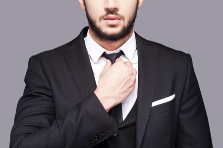 exceptional: Corporate confidence meets exceptional style. Cropped image of fashionable young man adjusting his necktie while standing against grey