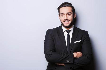 hombre de negocios: Exitoso hombre de negocios. Retrato de hombre joven confía en ropa formal mirando a la cámara y sonriendo mientras mantiene los brazos cruzados y de pie contra gris Foto de archivo