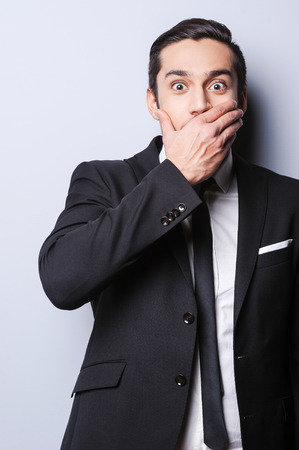 surprise face: Hope, I do not say too much. Excited young man in formal wear covering mouth with hand and looking at camera while standing against grey