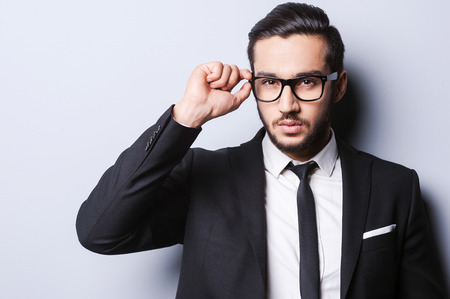 anteojos: Tomar la vida en serio. Retrato de hombre joven y guapo en ropa formal ajustándose las gafas de pie sobre gris