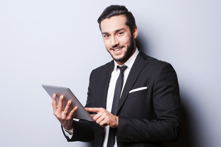 beard man: Confident and successful. Confident young man in formal wear working on digital tablet and smiling while standing against grey  Stock Photo