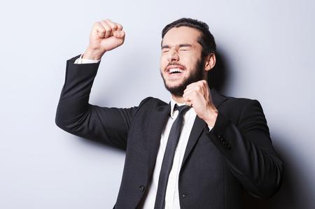 puños cerrados: Exitoso hombre de negocios. Hombre maduro feliz en ropa formal gesticulando y mantener los ojos cerrados mientras está de pie en contra de gris