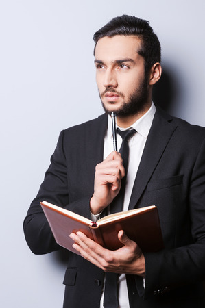 Serious thoughts. Thoughtful young man in formal wear holding note pad and touching his chin with pen while standing against grey  photo