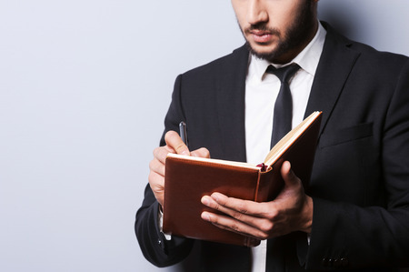 i pad: I need some fresh ideas. Close-up of young man in formal wear holding note pad and writing in it with pen while standing against grey  Stock Photo