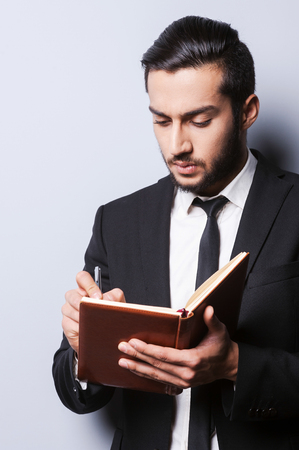 i pad: I need some fresh ideas. Concentrated young man in formal wear holding note pad and writing in it with pen while standing against grey  Stock Photo