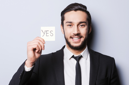 I will say yes! Handsome young man in formal wear holding adhesive note while standing against grey