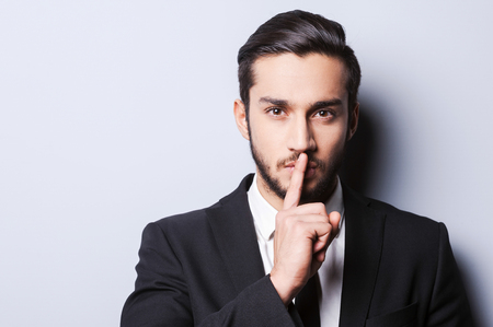 Keep my secret!  Serious young man in formal wear holding finger on lips and looking at camera while standing against grey