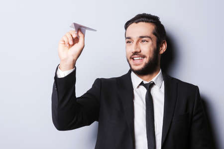 corporate airplane: Businessman with paper airplane. Playful young man in formal wear holding paper airplane and smiling while standing against grey  Stock Photo