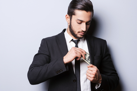 putting money in pocket: I love money and they love me. Handsome young man in formal wear putting money in his pocket while standing against grey