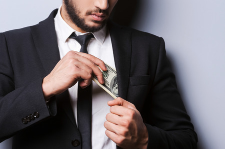 Wealthy handsome. Close-up of young man in formal wear putting money in his pocket while standing against grey  photo