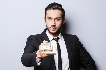 Come to work and get your first salary. Close-up of young man in formalwear stretching out money while standing against grey background photo