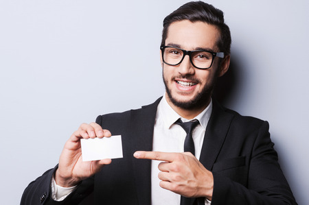 business person: Just call this number! Handsome young man in formalwear stretching out a business card while standing against grey background Stock Photo