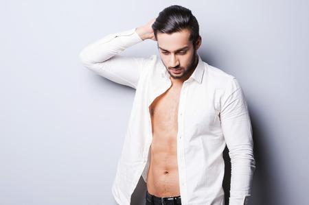 Real macho. Handsome young man in unbuttoned shirt holding hand on head while standing against grey  photo