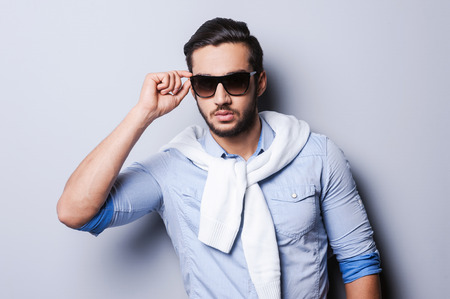 Style is my game. Handsome young man in blue shirt adjusting sunglasses while standing against grey background photo