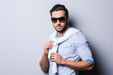 Casual cool. Handsome young man in blue shirt tying sweater on her shoulders while standing against grey background photo