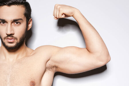 only the biceps: Perfect bicep. Close-up of muscular man showing his perfect bicep while standing against grey background Stock Photo