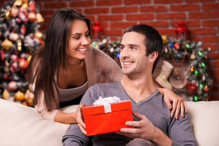 Christmas is time for giving. Beautiful young woman giving a red gift box to her boyfriend and smiling with Christmas Tree in the background photo