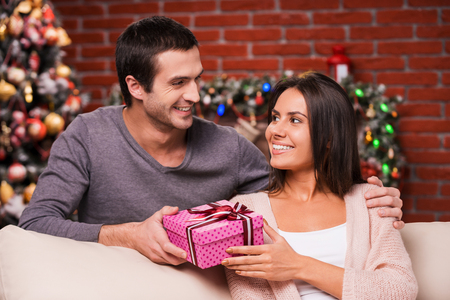Christmas present for her. Handsome young man giving a red gift box to his girlfriend and smiling with Christmas Tree in the background photo