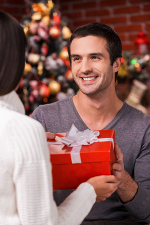 What a surprise! Rear view of young man giving a red gift box to his girlfriend with Christmas Tree in the background photo