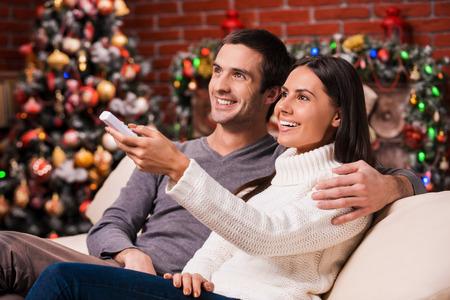 pareja viendo tv: Ver la Navidad muestra juntos. Vista lateral de la hermosa joven pareja amorosa uni�n entre s� y sonriendo mientras ve la televisi�n junto con el �rbol de Navidad en el fondo Foto de archivo
