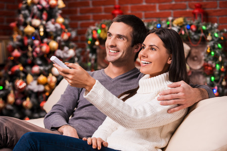 man watching tv: Watching Christmas shows together. Side view of beautiful young loving couple bonding to each other and smiling while watching TV together with Christmas Tree in the background