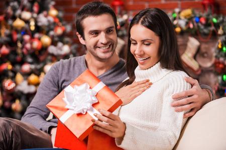 inauguracion: Qué gran sorpresa! Joven y bella mujer abriendo una caja de regalo y sonriendo mientras su novio sentado cerca de ella en el sofá con la decoración de navidad en el fondo Foto de archivo