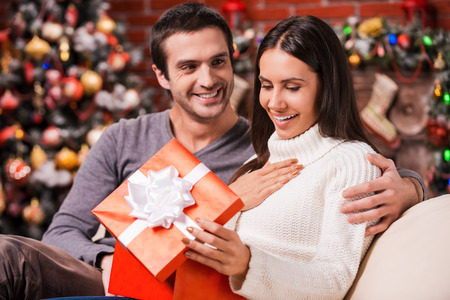 adult christmas: What a great surprise! Beautiful young woman opening a gift box and smiling while her boyfriend sitting close to her on the couch with Christmas decoration in the background