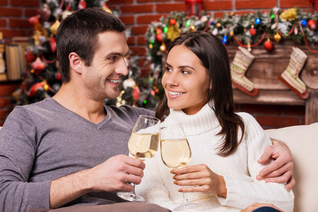 Happy New Year! Beautiful young loving couple bonding to each other and holding wine glasses with Christmas Tree photo