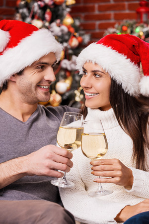 Happy New Year! Happy young loving couple in Santa hats bonding to each other and holding wine glasses with Christmas Tree in the background photo