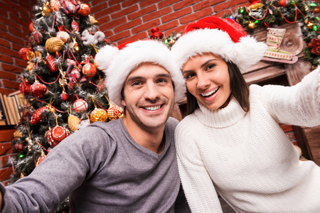 happy moment: Capturing a happy moment. Beautiful young loving couple bonding to each other and smiling while making selfie with Christmas Tree  Stock Photo