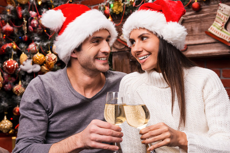 Cheers! Happy young loving couple in Santa hats bonding to each other and cheering with wine and with Christmas Tree in the background photo